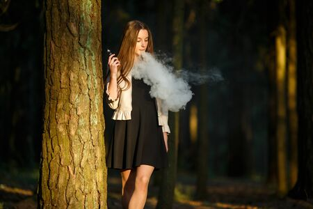 Vape teenager. Young cute girl in casual clothes smokes an electronic cigarette outdoors in the forest at sunset in summer. Bad habit that is harmful to health. Vaping activity. Banque d'images - 132014493