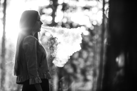 Vape teenager. Young cute girl in casual clothes smokes an electronic cigarette outdoors in the forest at sunset in summer. Bad habit that is harmful to health. Vaping activity. Black and white. Banque d'images - 132013721