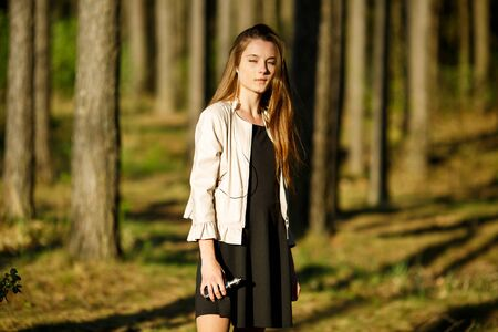 Vape teenager. Young cute girl in casual clothes smokes an electronic cigarette outdoors in the forest at sunset in summer. Bad habit that is harmful to health. Vaping activity. Banque d'images - 133007917