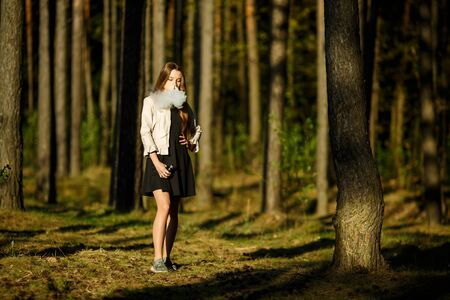 Vape teenager. Young cute girl in casual clothes smokes an electronic cigarette outdoors in the forest at sunset in summer. Bad habit that is harmful to health. Vaping activity. Banque d'images - 132014591