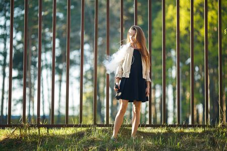 Vape teenager. Young cute girl in casual clothes smokes an electronic cigarette in front of a metal fence outdoors in the forest at sunset in summer. Bad habit. Stop vaping. Banque d'images - 133007919