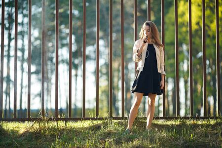 Vape teenager. Young cute girl in casual clothes smokes an electronic cigarette in front of a metal fence outdoors in the forest at sunset in summer. Bad habit. Stop vaping. Banque d'images - 133007921