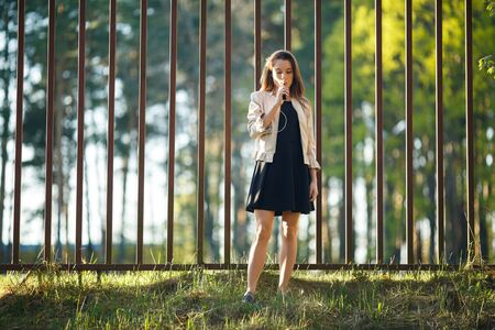Vape teenager. Young cute girl in casual clothes smokes an electronic cigarette in front of a metal fence outdoors in the forest at sunset in summer. Bad habit. Stop vaping. Banque d'images - 133007922