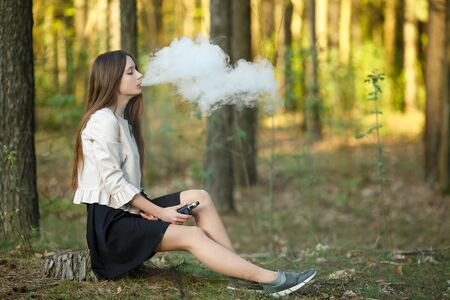 Vape teenager. Young cute girl in casual clothes smokes an electronic cigarette outdoors in the forest at sunset in summer. Bad habit that is harmful to health. Vaping activity. Banque d'images - 132013897