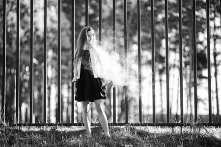 Vape teenager. Young cute girl in casual clothes smokes an electronic cigarette in front of a metal fence outdoors in the forest at sunset in summer. Bad habit. Stop vaping. Black and white. Banque d'images - 132013976