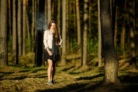 Vape teenager. Young cute girl in casual clothes smokes an electronic cigarette outdoors in the forest at sunset in summer. Bad habit that is harmful to health. Vaping activity. Banque d'images - 132014431