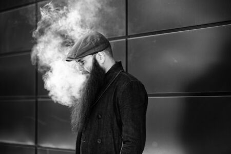 Vape bearded man. An adult man with a very long beard in a cap and sunglasses smokes an electronic cigarette on a sunny day outside. Bad habit that is harmful to health. Black and white. Banque d'images - 132017605