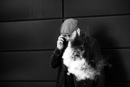 Vape bearded man. An adult man with a very long beard in a cap and sunglasses smokes an electronic cigarette and talkes on the mobie phone on a sunny day outside. Bad habit. Black and white. Banque d'images - 132016692