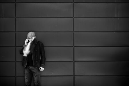 Vape bearded man. An adult man with a very long beard in a cap and sunglasses smokes an electronic cigarette and talkes on the mobie phone on a sunny day outside. Bad habit. Black and white. Banque d'images - 132016866