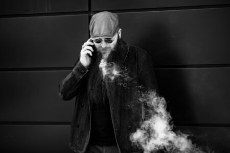 Vape bearded man. An adult man with a very long beard in a cap and sunglasses smokes an electronic cigarette and talkes on the mobie phone on a sunny day outside. Bad habit. Black and white. Banque d'images - 132017363