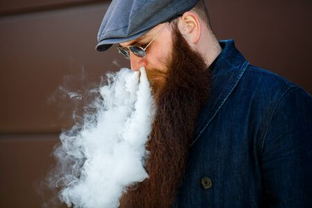 Vape bearded man. An adult man with a very long beard in a cap and sunglasses smokes an electronic cigarette on a sunny day outside. Bad habit that is harmful to health. Banque d'images - 132017525