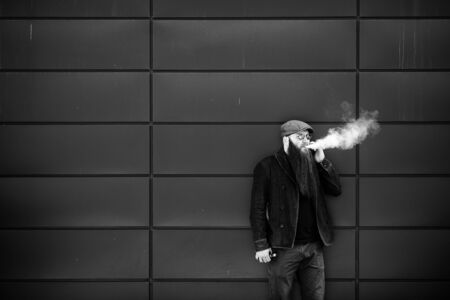 Vape bearded man. An adult man with a very long beard in a cap and sunglasses smokes an electronic cigarette and talkes on the mobie phone on a sunny day outside. Bad habit. Black and white. Banque d'images - 132017719