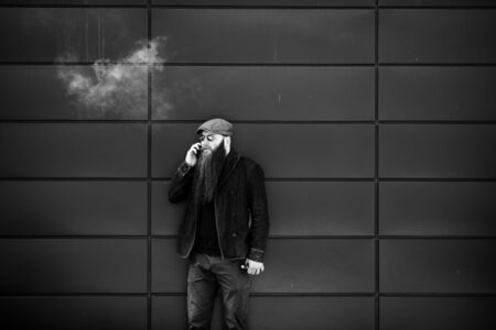 Vape bearded man. An adult man with a very long beard in a cap and sunglasses smokes an electronic cigarette and talkes on the mobie phone on a sunny day outside. Bad habit. Black and white. Banque d'images - 132017368