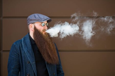 Vape bearded man. An adult man with a very long beard in a cap and sunglasses smokes an electronic cigarette on a sunny day outside. Bad habit that is harmful to health. Banque d'images - 132017798