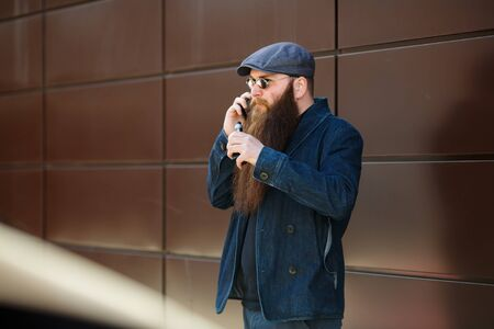 Vape bearded man. An adult man with a very long beard in a cap and sunglasses smokes an electronic cigarette and talkes on the mobie phone on a sunny day outside. Bad habit that is harmful to health. Banque d'images - 132017826
