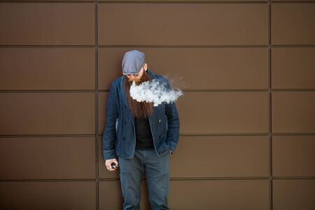 Vape bearded man. An adult man with a very long beard in a cap and sunglasses smokes an electronic cigarette on a sunny day outside. Bad habit that is harmful to health. Banque d'images - 132017640