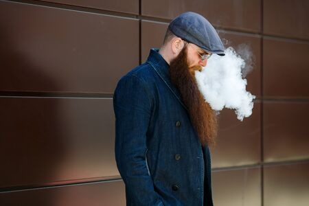 Vape bearded man. An adult man with a very long beard in a cap and sunglasses smokes an electronic cigarette on a sunny day outside. Bad habit that is harmful to health. Banque d'images - 132019549