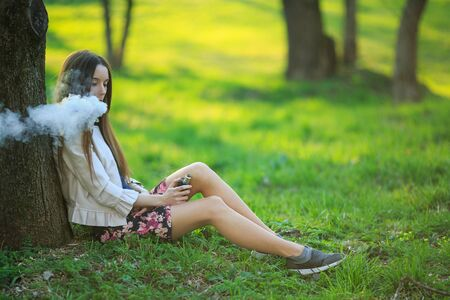 Vape teenager. Young cute girl in a dress sits near a tree and smokes an electronic cigarette outdoors in a park in spring. Bad habit that is harmful to health. Vaping activity. Banque d'images - 132026083