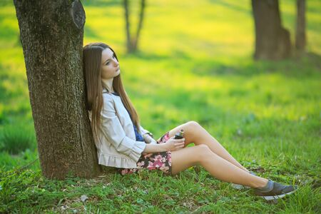 Vape teenager. Young cute girl in a dress sits near a tree and smokes an electronic cigarette outdoors in a park in spring. Bad habit that is harmful to health. Vaping activity. Banque d'images - 132025426