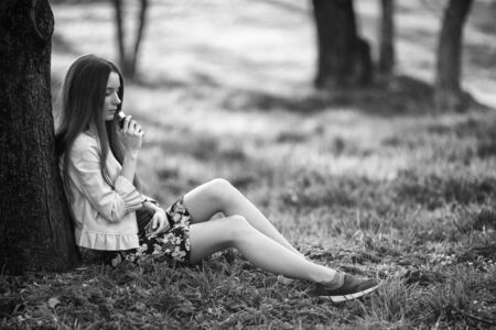 Vape teenager. Young cute girl in a dress sits near a tree and smokes an electronic cigarette outdoors in a park in spring. Bad habit that is harmful to health. Vaping activity. Banque d'images - 132025182