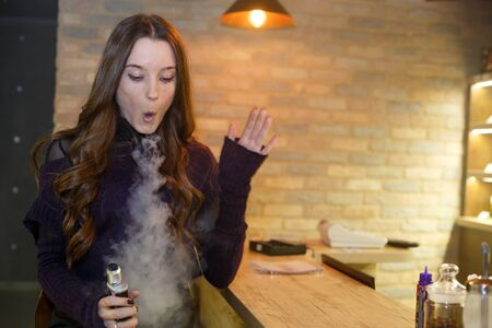 Vape teenager with problem skin. Young pretty white girl smoking an electronic cigaretter. Bad habit. Close up. Banque d'images - 133007927