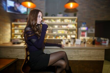 Vape teenager with problem skin. Young pretty white girl smoking an electronic cigarette in vape bar. Bad habit. Banque d'images - 132032501