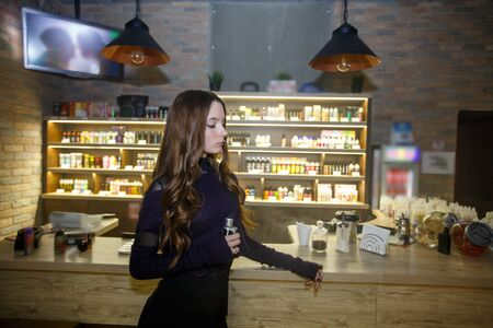 Vape teenager with problem skin. Young pretty white girl smoking an electronic cigarette in vape bar. Bad habit. Banque d'images - 132032137