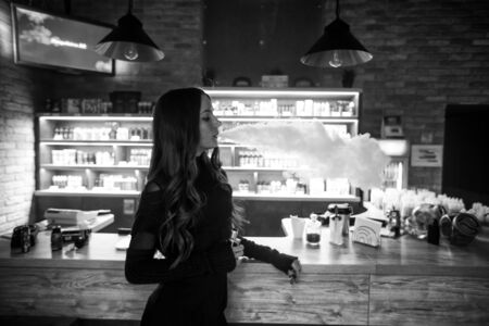 Vaping teenager. Young pretty white girl smoking an electronic cigarette  in vape bar. Bad habit. Black and white. Banque d'images - 132031662