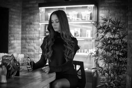 Vaping teenager. Young pretty white girl smoking an electronic cigarette  in vape bar. Bad habit. Black and white. Banque d'images - 132032373