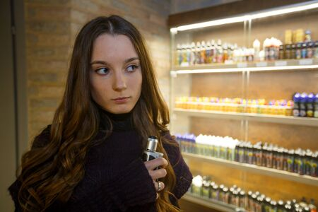 Vape teenager with problem skin. Young pretty white girl smoking an electronic cigaretter. Bad habit. Close up. Banque d'images - 132031738