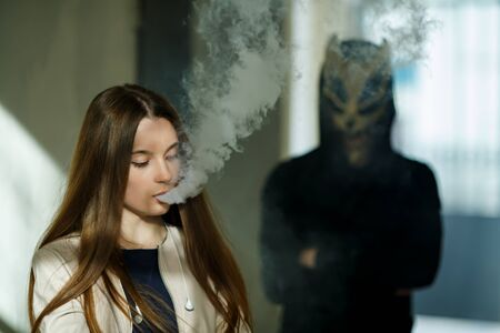 Vape teenager and death. Young cute girl in a dress an electronic cigarette near the wall in front of monster in the background outdoors in spring. Bad habit that is harmful to health. Vaping activity Banque d'images - 133007936