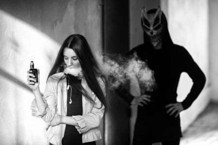 Vape teenager and death. Young cute girl in a dress an electronic cigarette near the wall in front of monster in the background outdoors in spring. Vaping activity. Black and white. Banque d'images - 133007937
