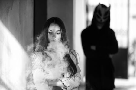Vape teenager and death. Young cute girl in a dress an electronic cigarette near the wall in front of monster in the background outdoors in spring. Vaping activity. Black and white. Banque d'images - 133007949