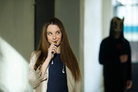 Vape teenager and death. Young cute girl in a dress an electronic cigarette near the wall in front of monster in the background outdoors in spring. Bad habit that is harmful to health. Vaping activity Banque d'images - 133007950
