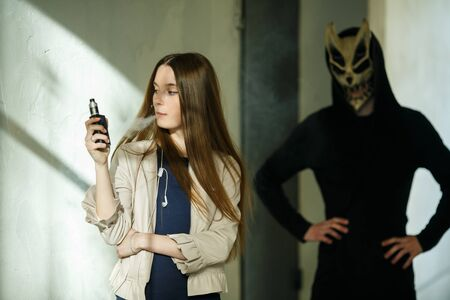 Vape teenager and death. Young cute girl in a dress an electronic cigarette near the wall in front of monster in the background outdoors in spring. Bad habit that is harmful to health. Vaping activity Banque d'images - 133559556