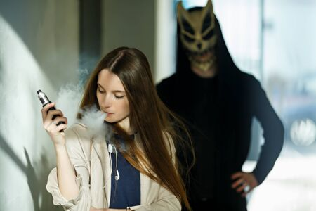 Vape teenager and death. Young cute girl in a dress an electronic cigarette near the wall in front of monster in the background outdoors in spring. Bad habit that is harmful to health. Vaping activity Banque d'images - 133559557