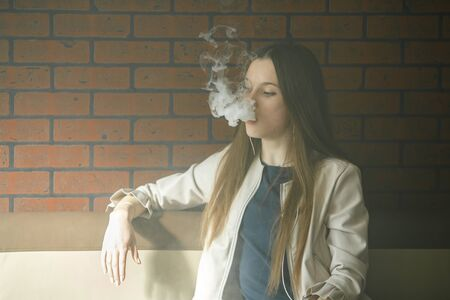 Vaping teenager. Young pretty white girl smoking an electronic cigarette in vape bar. Bad habit. Banque d'images - 133559559
