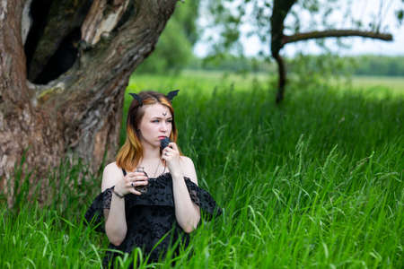 Young beautiful witch in black dress conducts a ceremony in a green forest on a summer day. Modern witchcraft.