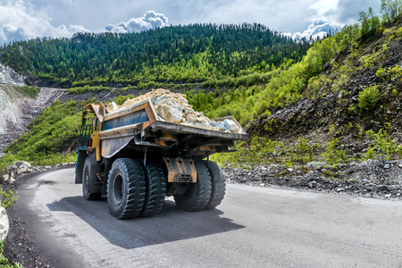 the dump truck carries the stones on the road Stock Photo