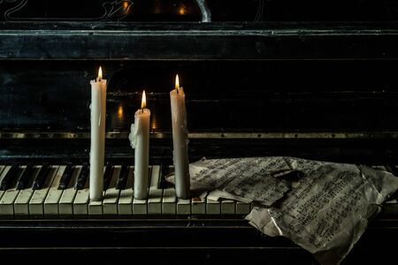 lit: Candles are lit on the piano with music sheets
