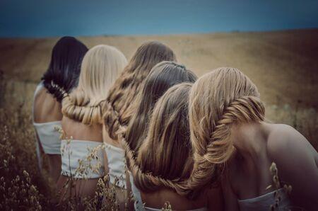 pelirrojas: Girls blondes, redheads and brunettes closed hair in summer field Foto de archivo