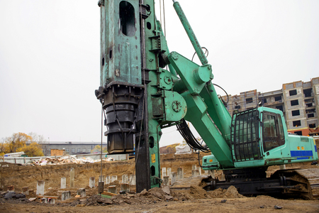 piling: Machine for the piling works at a construction site near the house Stock Photo