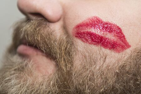 A man with beard that had some fun and got a kiss trace on the cheek. Closeup