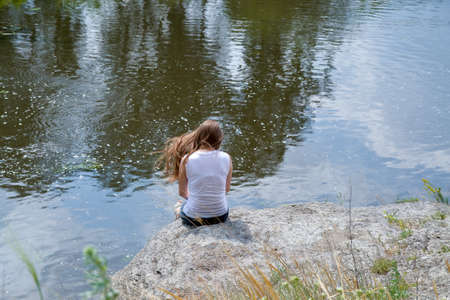 a lonely girl sits on a rock near the river