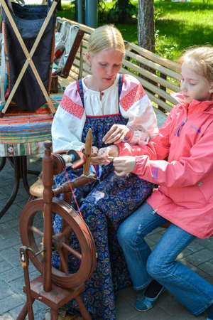 Chelyabinsk Russia June 12 2015 holiday Russia day a woman teaches a girl to make yarn on an old spinning wheel in a Park to remember the traditions 新聞圖片