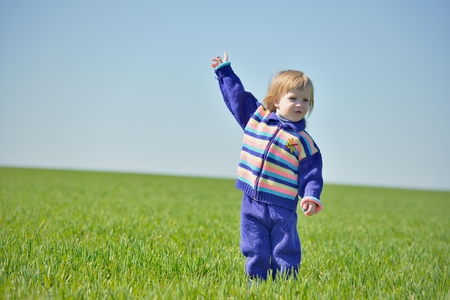 raised hand: Little girl with raised hand in a field