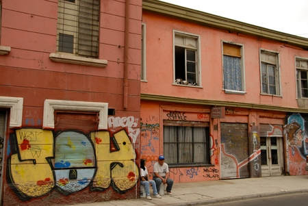 observers: A couple of people sitting on the sidelines for a pink house with graffiti