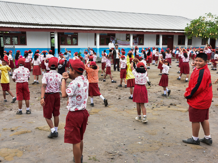 indonesian biodiversity: Students in maroon uniforms are morning exercises outside the school (Sumatra, Indonesia) Editorial