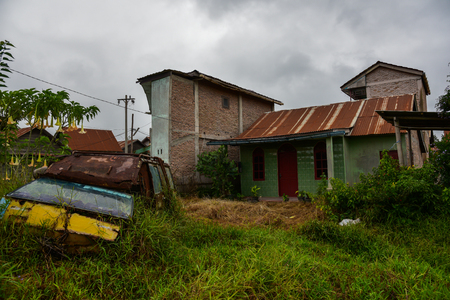 malay village: Wooden houses and abandoned the car after the evacuation of people are due to the volcano (Sumatra, Indonesia) Stock Photo