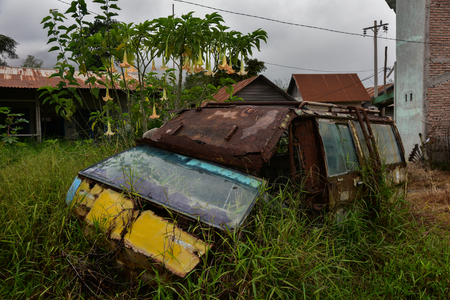 malay village: Old rusty car is after the evacuation of people due to the volcano (Sumatra, Indonesia) Stock Photo